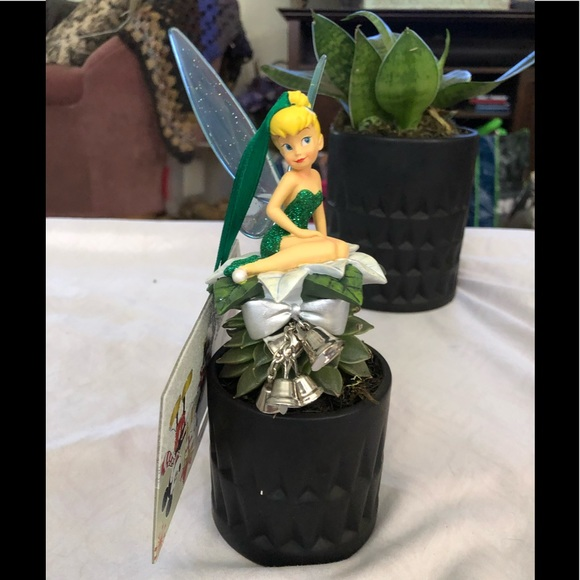 Disney's Tinkerbell seated on poinsettia